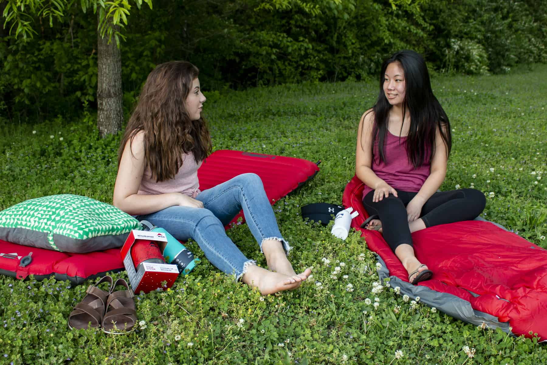 Two girls camping in green grass talking