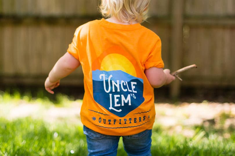 Baby with Uncle Lem's Outfitters tshirt playing outside